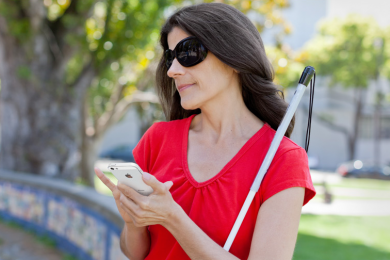 blind female with walking cane using apple iphone