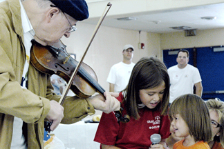 older man playing violin for children