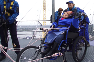 woman in wheelchair being pushed over a bridge