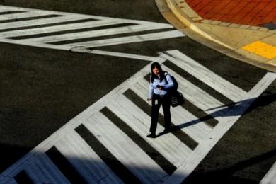 aerial view of woman walking across crosswalk