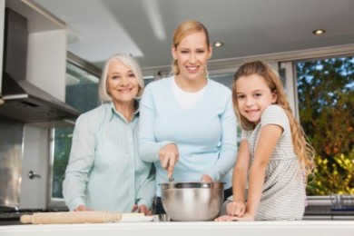 an older woman, adult woman, and female child posing in a kitchen
