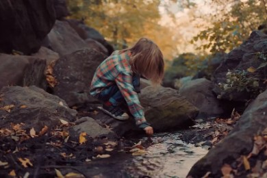 a young child squatting and reaching into a stream of water
