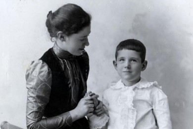 A teacher communicating with a student who is deafblind via the manual alphabet, circa 1894.