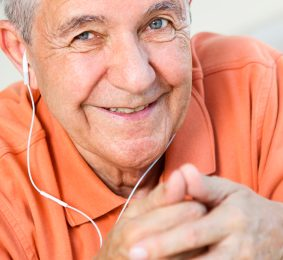 Caucasian smiling older man wearing headphones