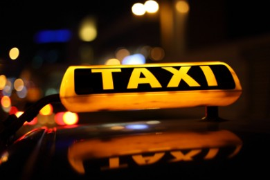 close up image of Yellow taxi sign on top of car at night