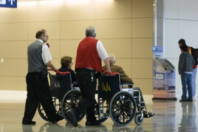 two wheelchair users being pushed through an airport