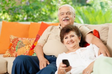 older couple sitting on couch watching TV