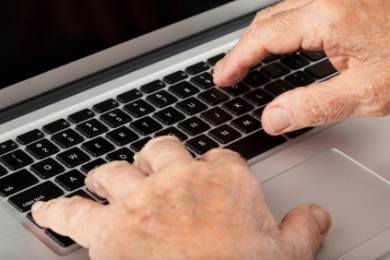 close up image of hands of an elderly person on a laptop keyboard