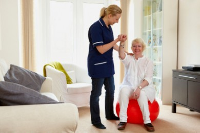 older woman sitting on an exercising ball with a nurse helping her keep balance
