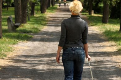 a blind person holding a cane and walking through a park