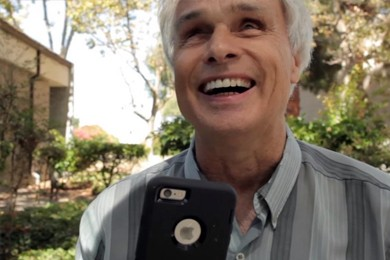 a blind man smiling as he listens to his phone