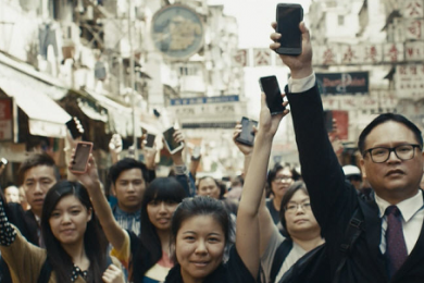 a group of people raising mobile devices in their hands