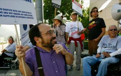 danny woodburn holding protest sign in a crowd of protesters