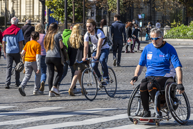 wheelchair user crossing a stone paved street