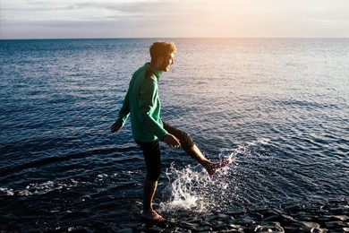 young man standing in sea kicking up water