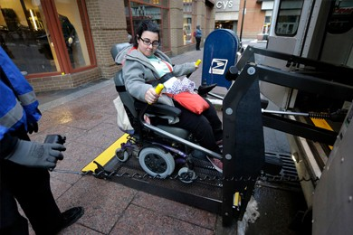 woman in wheelchair ascending bus ramp