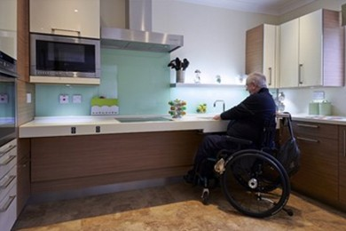 older man in wheelchair using sink