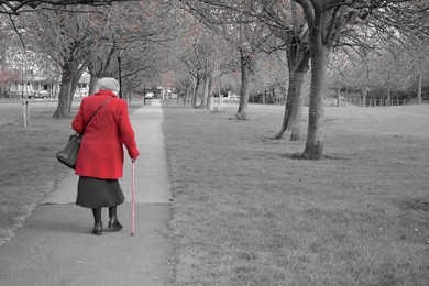 elderly woman with red coat and cane walking down sidewalk