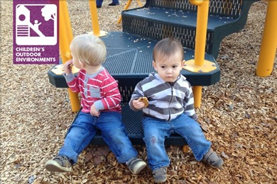 two toddlers sitting on playground