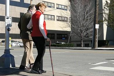 elderly couple standing at crosswalk