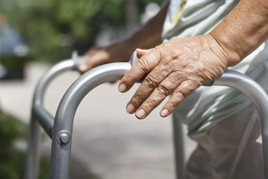 closeup of senior hands holding walking aid
