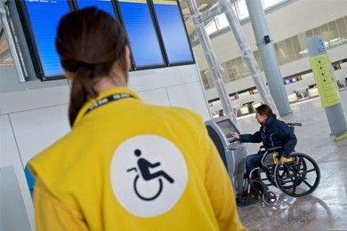 person in wheelchair using kiosk in airport
