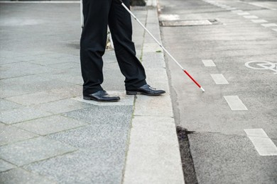 close up of a person's legs and walking cane on sidewalk