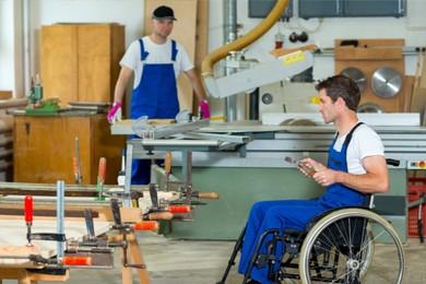 man in wheelchair working in workshop