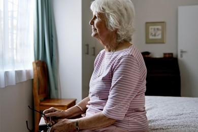 older woman sitting on bed looking out window