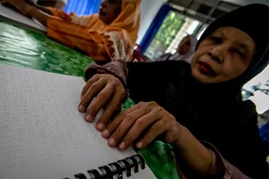 Blind people read braille Qur'ans at a disability rehabilitation centre in Indonesia. The centre cares for around 40 Muslim patients. Photograph: Y T Haryono/Barcroft Images