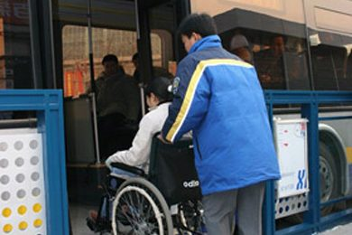 person in wheelchair being pushed up bus ramp