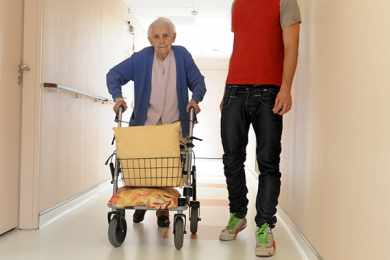elderly woman walking using a walker with younger man walking along side her