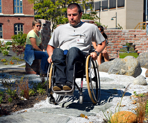 Wheelchair user travel through a outdoor garden on an uneven path