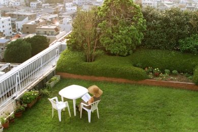 A woman reads on a rooftop garden in a residential area of Tokyo.