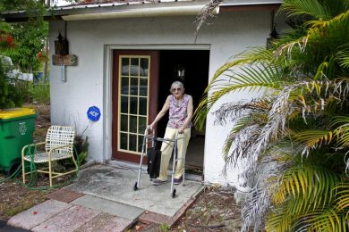 older adult in front of her home