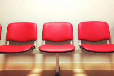 Armless, red chairs lined up against the wall.