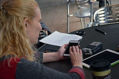 Young woman seated at a table using the audio app on a cell phone.