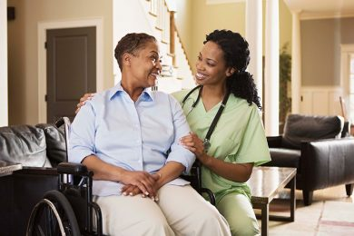 Health care professional holding elder women in wheelchair. The two are smiling at each other.