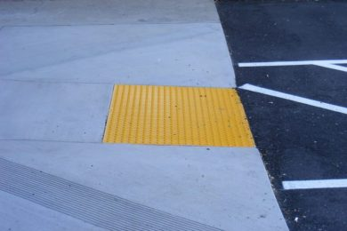 Yellow bumpy pavement, or detectible warning paver, placed at edge of sidewalk leading into the street.