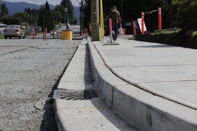 Corner curb of sidewalk with pedestrian walking