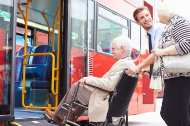 Young man assisting an elder couple onto a public transit bus.