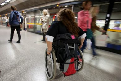 Disabled wheel chair user moving through a transit station