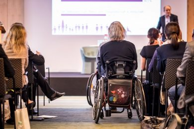 Photo from behind of a presentation with rowed seating, with a wheelchair placed in the center of the isle to show lack of planning.