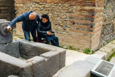 Individual in wheelchair being guided down the barrier free paths of the Pompeii Archaeological Site