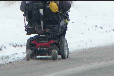 Wheeled mobility device driving on the side of the road, due to snow covered sidewalks
