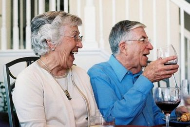 Elderly couple, laughing while drinking wine