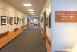 An orange sign in the Amherst Center for Senior Services hangs in front of a corridor to indicate which rooms and services are ahead.