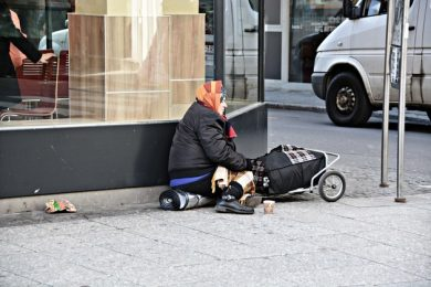 homeless women sitting on a street corner with her belongings