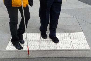 Two individuals, from the waist down, at the end of a curb, one is holding a white cane.
