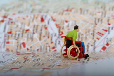 Plastic figure of a wheelchair user rolling over a paper map